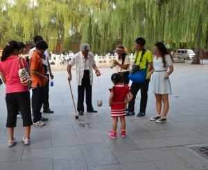 Seorang kakek yang menulis kaligrafi tulisan Cina