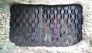 Makam dengan jeruji besi dan gembok
